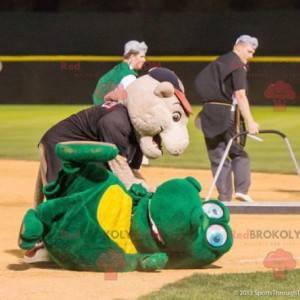 2 mascottes: een groene krokodil en een roze varken -