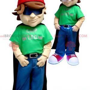 Mascotte del ragazzo con un mantello e un berretto -