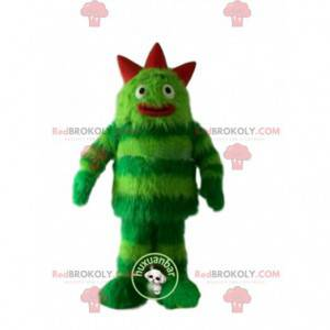 Monstro de mascote verde, cabeludo e divertido. Terno verde -