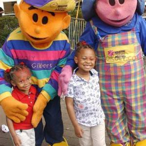 2 Maskottchen: ein rosa Mädchen und ein orangefarbener Junge -