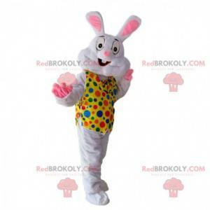 Mascote coelho branco com colete amarelo com pontos coloridos -