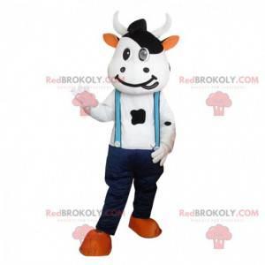Mascotte della mucca con jeans e bretelle. Pelle bovina gigante