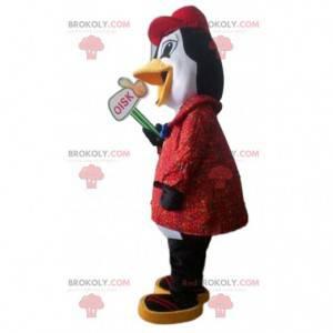 Mascota de pingüino blanco y negro con un abrigo rojo -