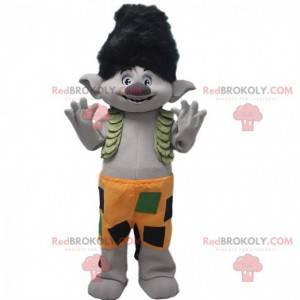Mascota troll gris con pelo negro y pantalones cortos naranjas