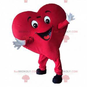 Mascota de corazón rojo gigante, traje romántico y sonriente -