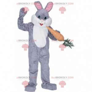 Grijs en wit konijn mascotte met een gigantische wortel -