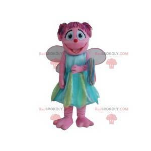 Mascota de hadas rosa con su bonito vestido azul y verde -
