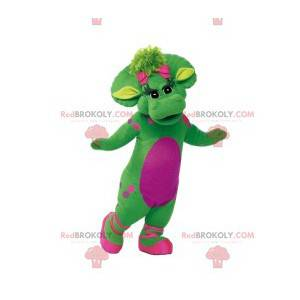 Green female dinosaur mascot with pink polka dots and her