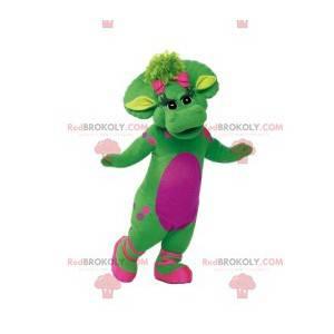 Mascote de dinossauro fêmea verde com bolinhas rosa e seu