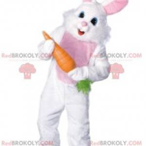 Fröhliches weißes Kaninchenmaskottchen, das eine große Karotte