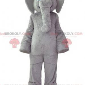 Šedý slon maskot s měkkým kabátem a širokým úsměvem -