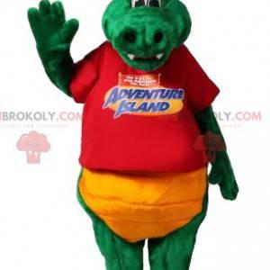 Zelený maskot dinosaura s červeným tričkem a žlutými šortkami -
