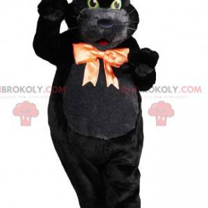 Black cat macsotte with green eyes with its orange bow -