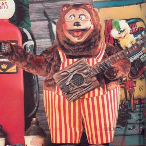 Big brown bear mascot with red and yellow overalls -