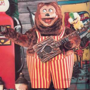 Velký medvěd hnědý maskot s červenými a žlutými kombinézy -
