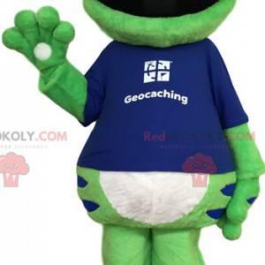 Grünes Froschmaskottchen mit einem blauen T-Shirt -