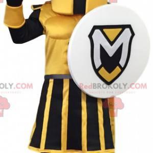 Gelbes und schwarzes Kriegermaskottchen mit einem Schild. -