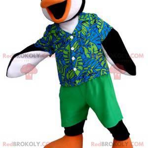 Svart hvit og oransje pingvin maskot med et fargerikt antrekk -