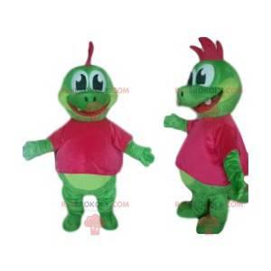 Mascotte dinosauro verde con un grazioso stemma fucsia -