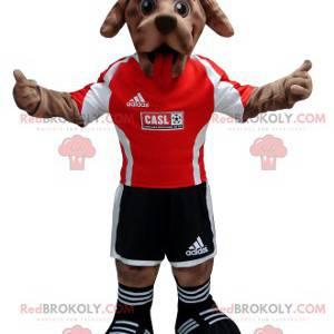 Braunes Hundemaskottchen im schwarzen und roten Fußballeroutfit