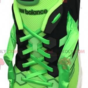 Grünes und schwarzes Sportschuhmaskottchen mit großen Augen -