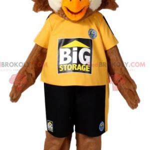 Maskot hnědého orla ve sportovním oblečení. Kostým orla -