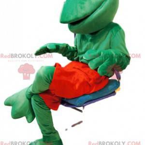 Mascota amigable rana verde con pantalones cortos rojos -