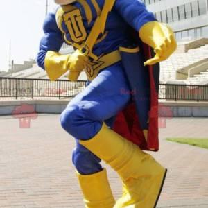Maskot superhrdiny ve žlutém a modrém oblečení s pláštěm -