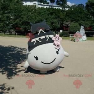 Maskottchen rundum und lächelnd mit einem Dach auf dem Kopf -