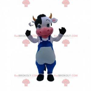 Czarno-biała krowa maskotka z niebieskim kombinezonem -