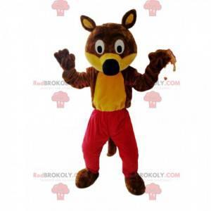 Lustiges braunes und gelbes Wolfsmaskottchen mit roten Hosen -