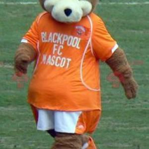 Hnědý a bílý medvídek maskot s oranžovým oblečením -