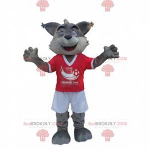 Szary wilk maskotka w czerwono-białej odzieży sportowej -