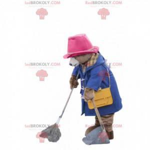 Niedźwiedź maskotka w niebieskim płaszczu i różowym kapeluszu -