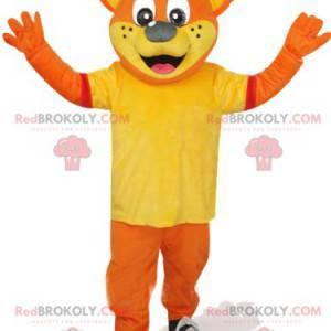 Oransje bjørnemaskot med gul t-skjorte og rød hette -