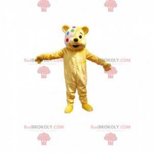 Malý žlutý medvěd maskot s různobarevným obvazem -