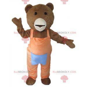 Braunes und weißes Bärenmaskottchen mit orangefarbenem Overall