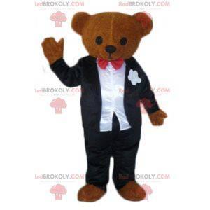 Maskot hnědý medvídek oblečený v černobílém kostýmu -