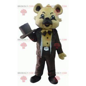 Béžový maskot koala v hnědém kostýmu s kloboukem -