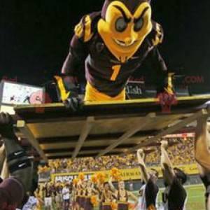 Czarno-żółty diabeł maskotka w odzieży sportowej -