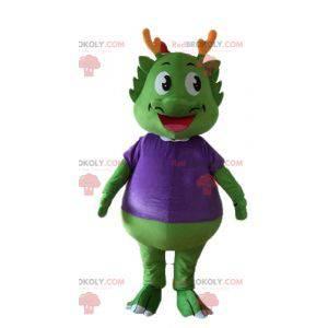 Zelený dinosaur maskot oblečený ve velmi teplé fialové -