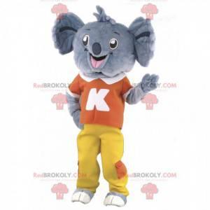 Mascote coala cinza com roupa vermelha e amarela -