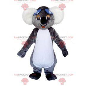 Mascotte koala grigio e bianco molto carino con gli occhiali -