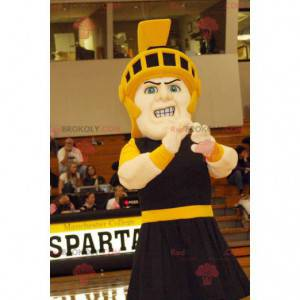 Mascote do cavaleiro em traje preto com capacete amarelo -