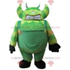 Maskot zelené monstrum ve velmi velkých a vtipných kombinézách