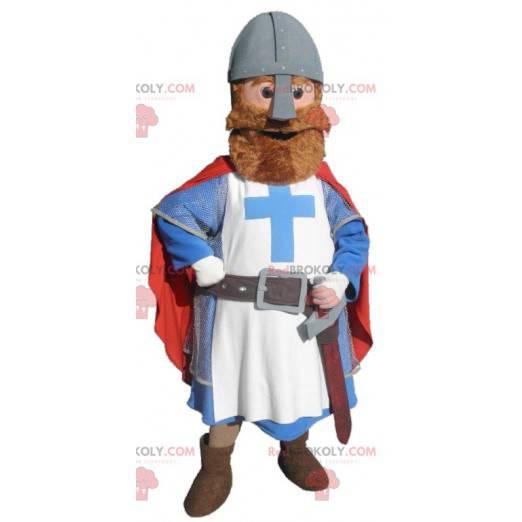 Maskotka rycerza ubrana w czerwony niebieski i biały -
