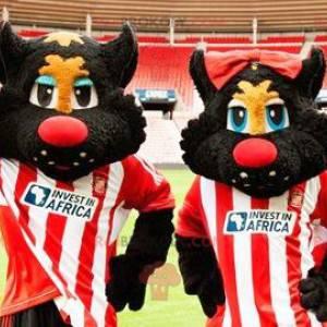 2 maskoti černých a červených koček ve sportovním oblečení -