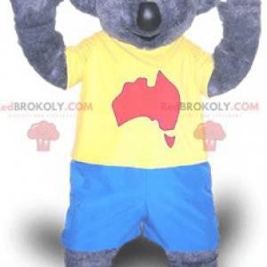 Graues Koalamaskottchen im blauen und gelben Outfit -