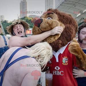 Braunes Löwenmaskottchen ganz haarig in roter Sportbekleidung -