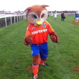 Maskot hnědé a bílé sovy v oranžové a modré oblečení -